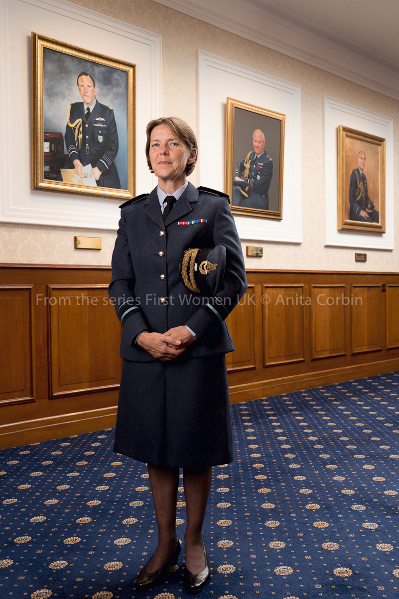 A woman wearing RAF uniform standing in a room with blue carpets and three large portraits hung on the hall behind.