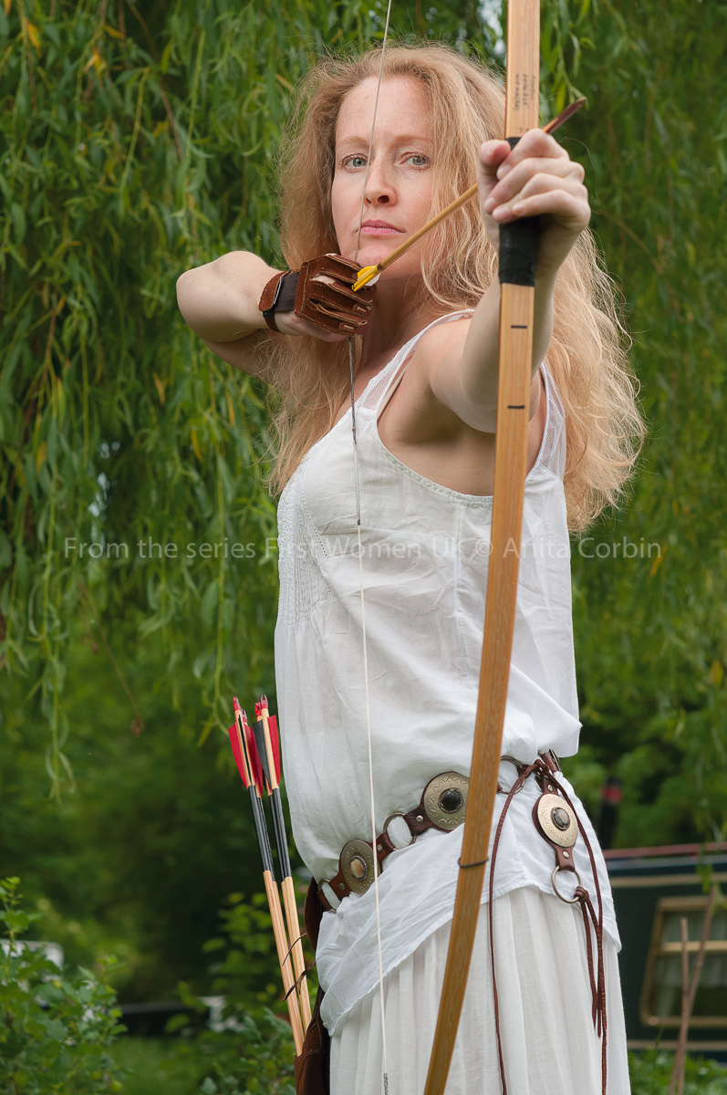 A woman in a white top firing a bow and arrow outdoors.