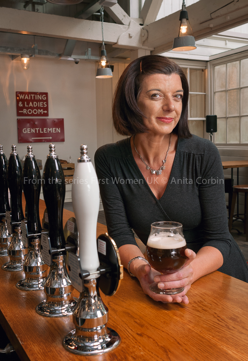 A woman sitting at a bar holding a glass of beer.
