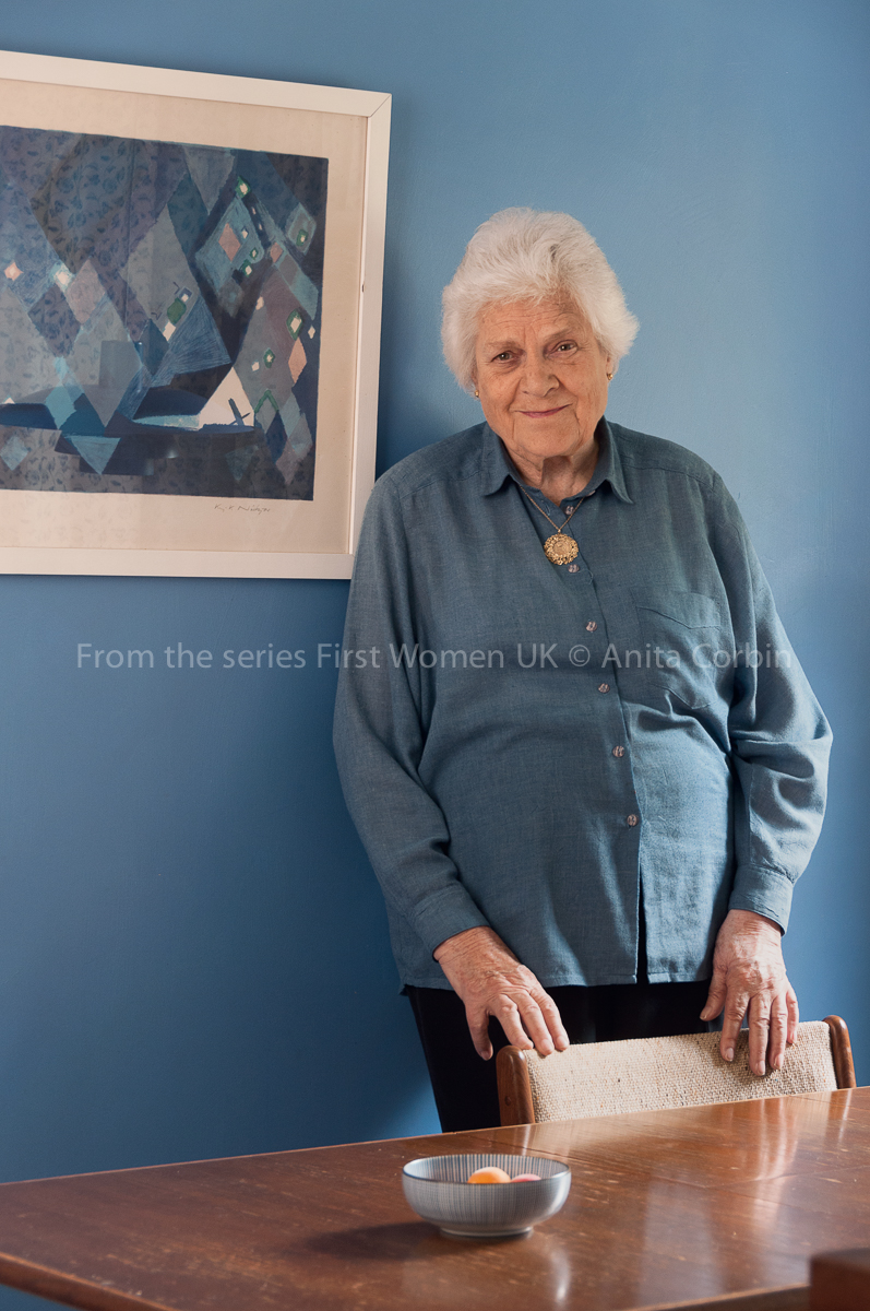 A woman wearing a blue shirt standing behind a table with her hands on the back of a chair. She is standing in front of a blue wall with a blue artwork framed on the wall.