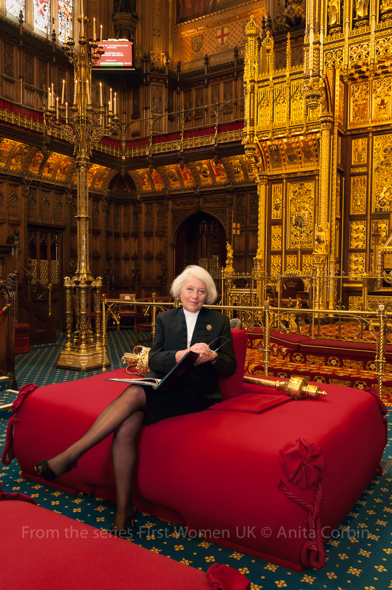 A woman sitting on a large red cushioned seat in the House of Lords.