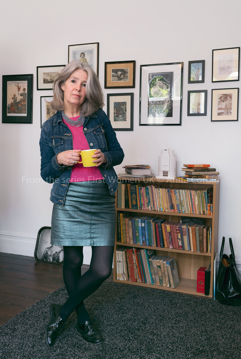 A woman wearing a denim skirt, denim jacket and pink top holding a yellow mug and standing in front of a bookshelf.