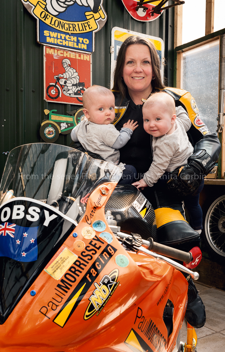 A woman sitting on an orange motorbike with two babies in her arms.