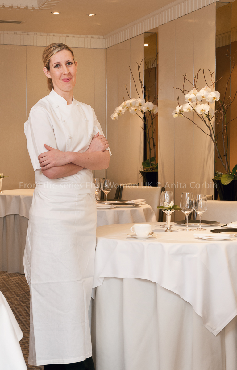 A woman wearing a white chef's outfit with her arms crossed standing next to a small round table with a white tablecloth.