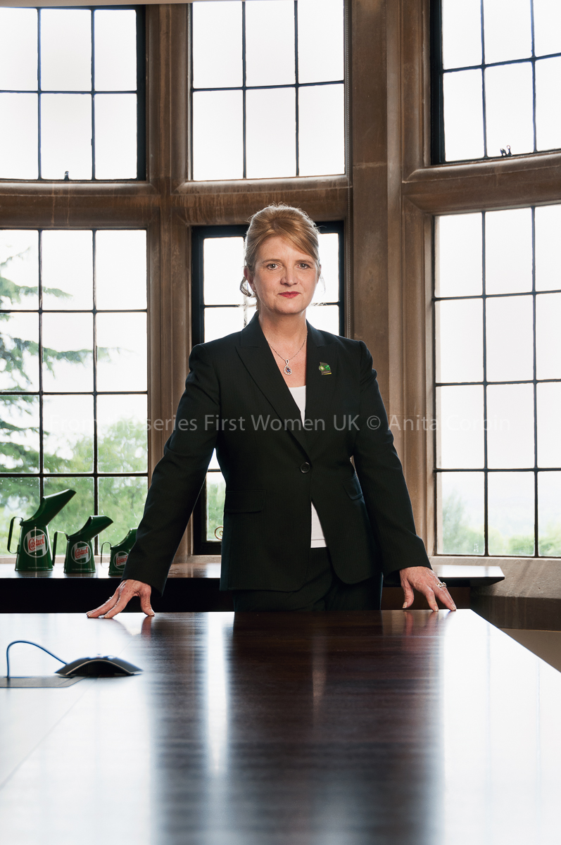 A woman wearing a black suit standing behind a large wooden desk with six window panes behind her.