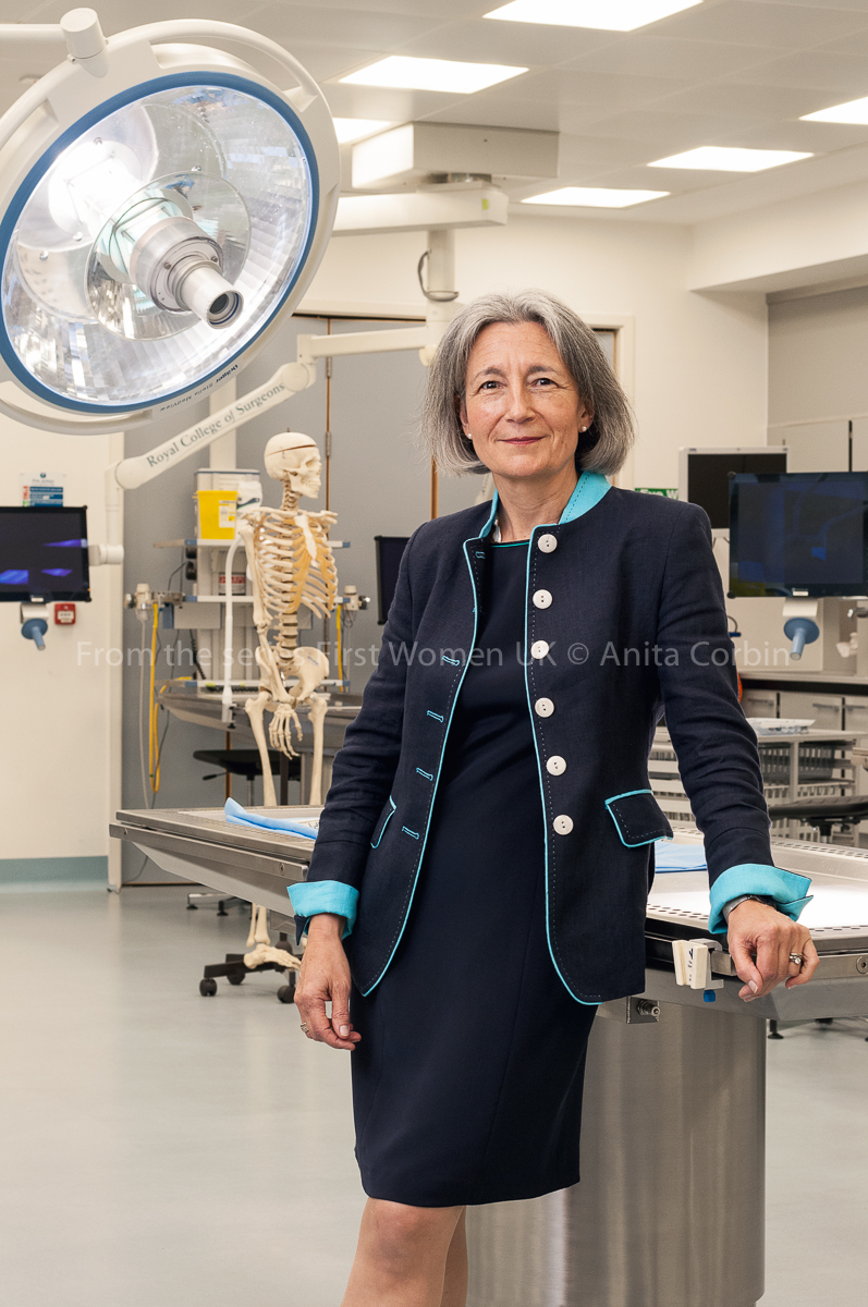 A woman wearing a navy blue dress and matching blazer standing in an operating theatre.