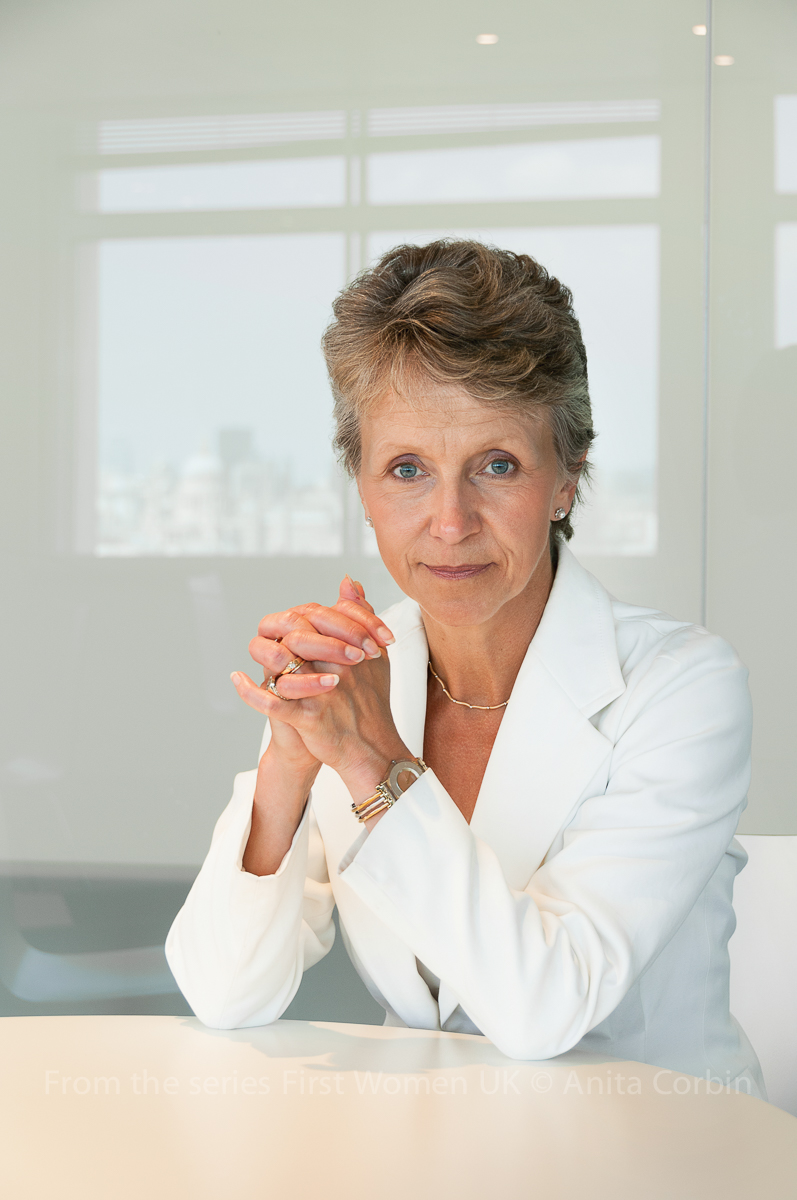 A woman wearing a white blazer sitting with her elbows on a round white table in front of a white gloss wall.