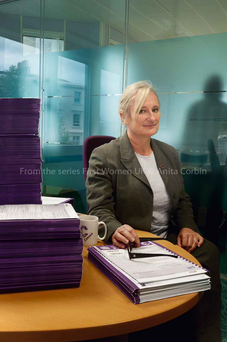 A woman sitting at a round table with stacks of purple files in front of her.