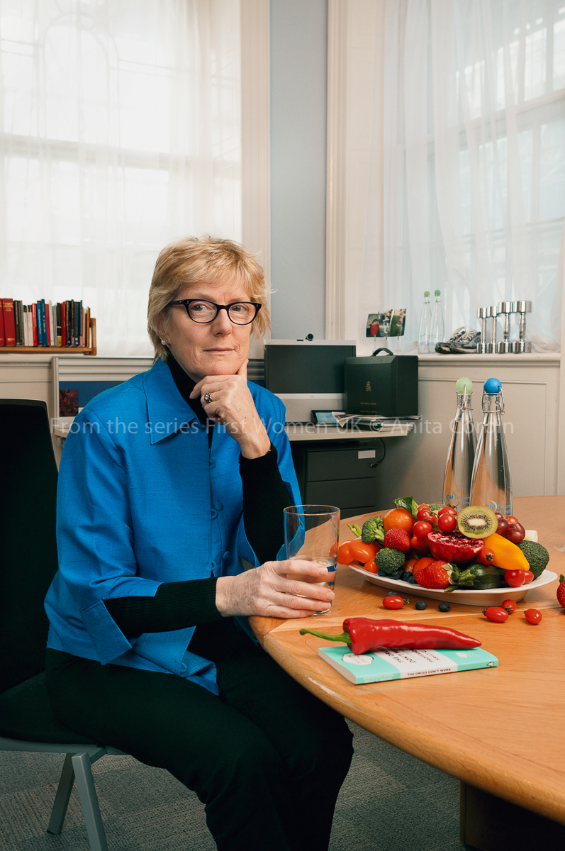 A woman wearing a bright blue shirt, black trousers and glasses sitting at a stable with a large bowl of fruits and vegetables with a glass of water in her hand.