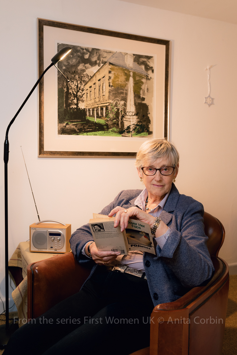 A woman sitting in a brown leather armchair holding a book. On the table beside her is a radio and a lamp standing on the floor next to her. A framed painting of a building is hung on the wall behind her.