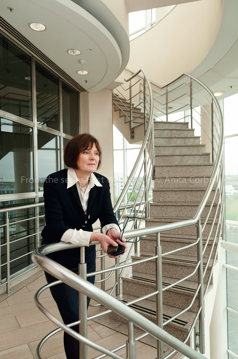 A woman standing with her hands resting on a railing standing at the bottom of a curved staircase in a glass building.