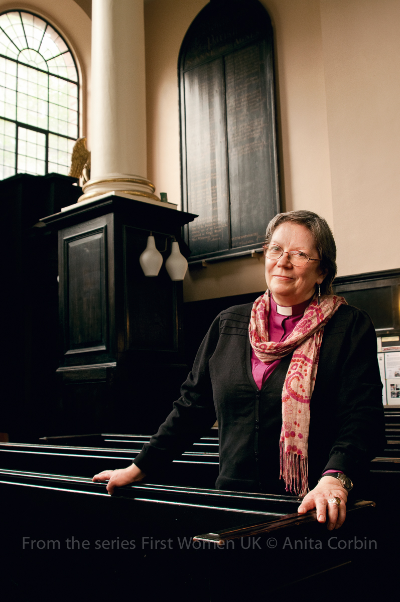 A woman wearing a black cardigan and pink scarf standing in a church.