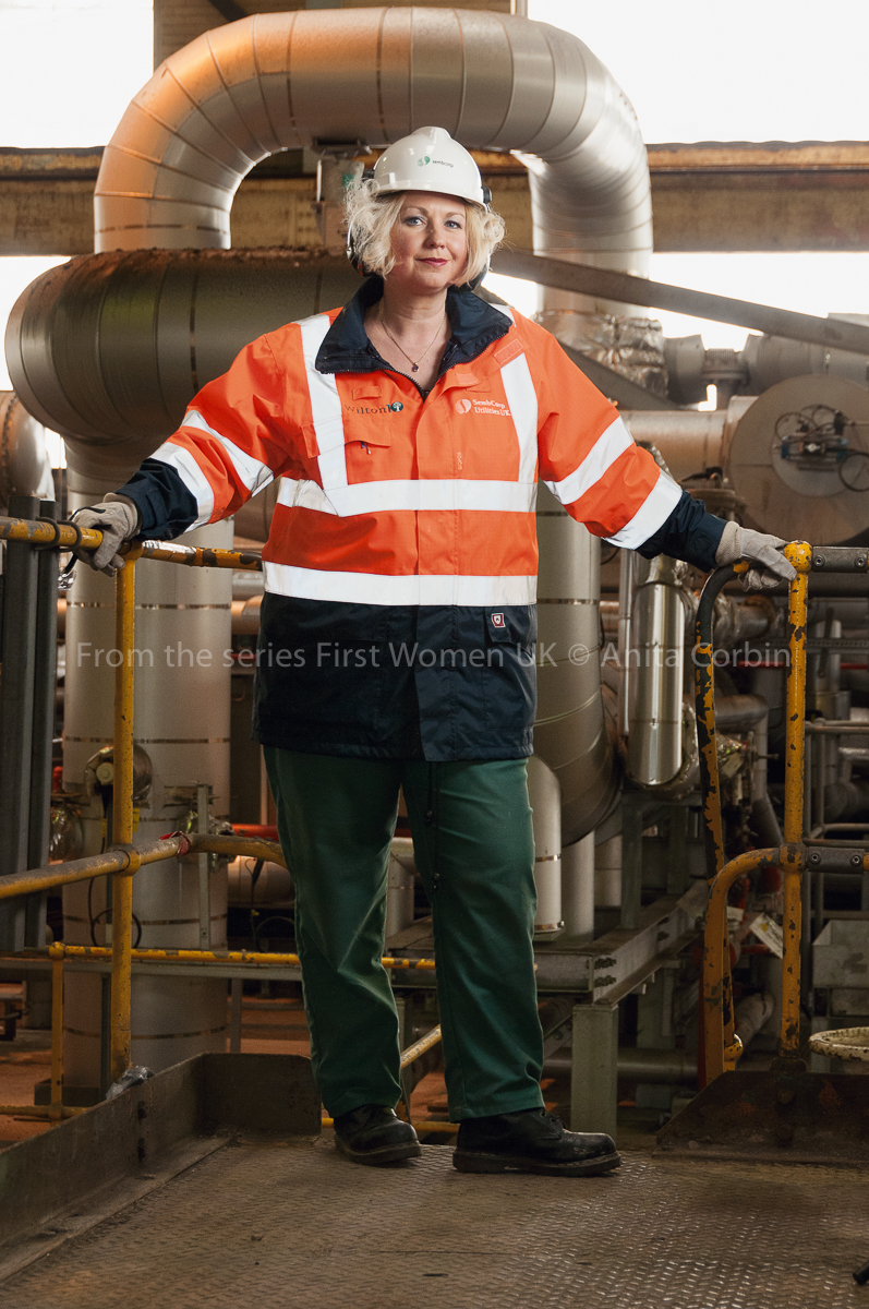 A woman wearing an orange and navy blue waterproof jacket and a white hard hat standing in front of large pipes.