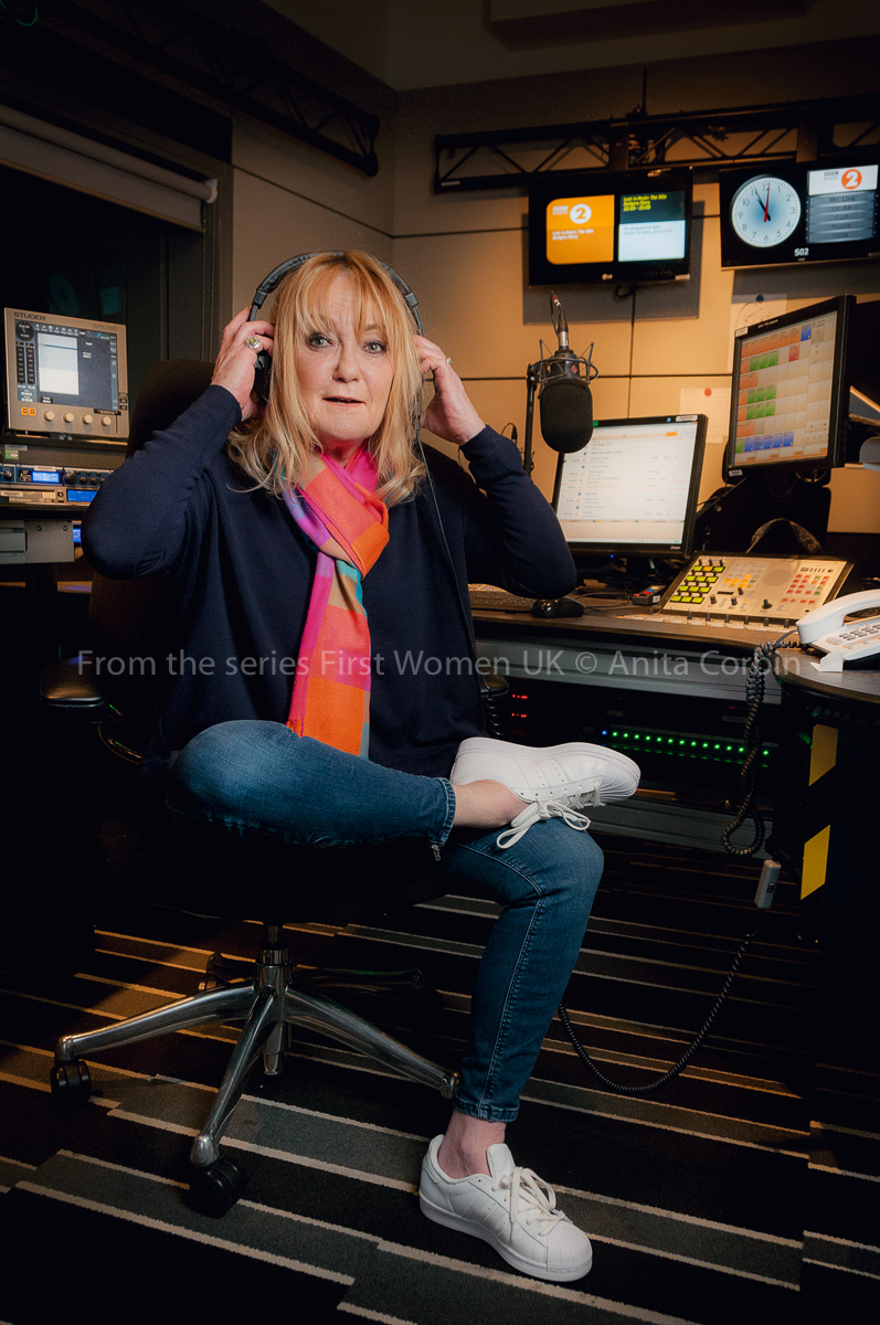 A woman wearing jeans and a pink and orange scarf with one foot on the other knee. She is putting a pair of headphones on her head and sitting in a DJ booth.