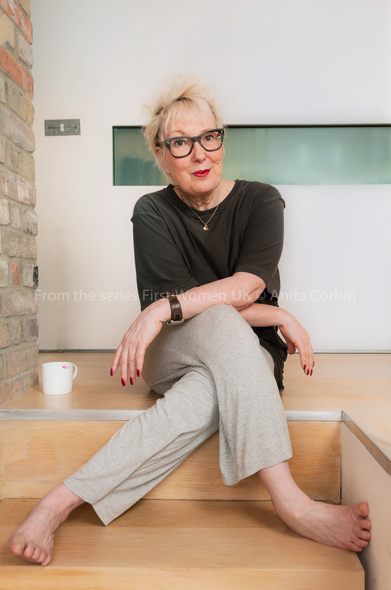 A woman sitting on a step indoors with her legs and arms crossed. She is wearing glasses, a dark top and beige trousers. A white mug is placed on the step next to her.