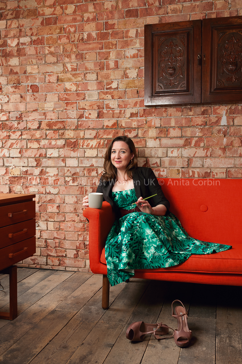 A woman wearing a green dress and black blazer sitting on a red sofa in front of a brick wall. She is holding a grey mug in one hand. A pair of high heeled shoes are scattered on the floor in front.