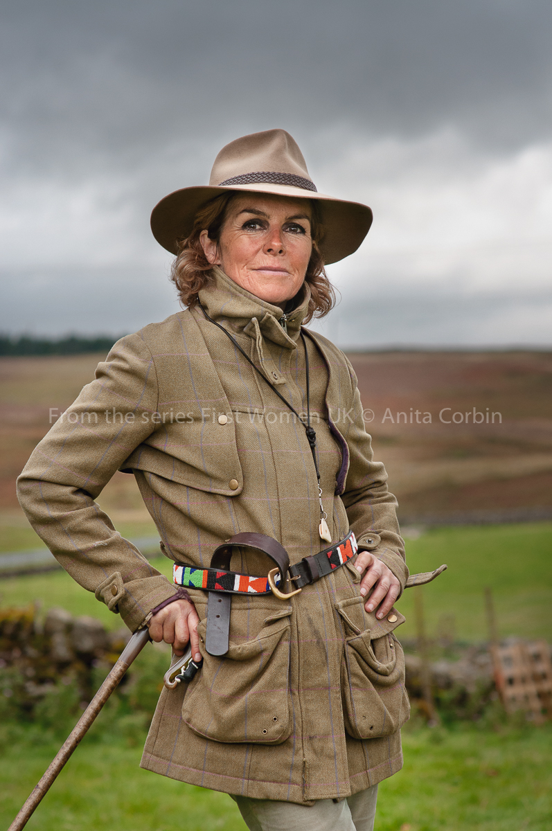 A woman wearing a beige jacket and hat with a multicoloured belt.