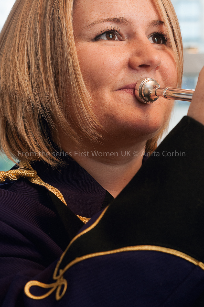 A woman with short blonde hair playing the cornet.