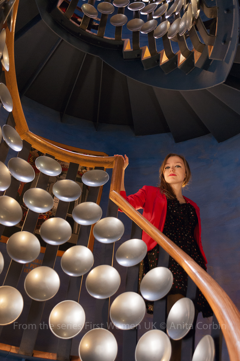 A woman wearing a red blazer standing holding the railing of a curved staircase. The banisters are decorated with silver disks.