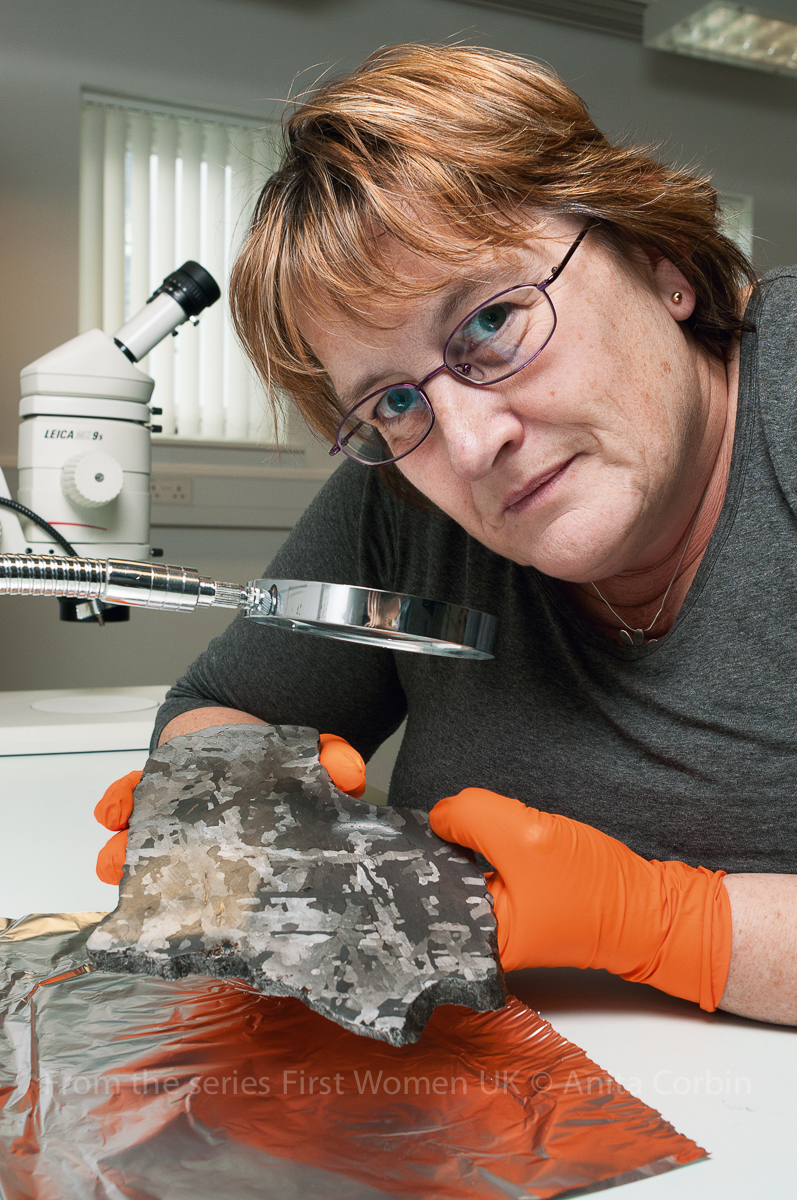 A woman wearing bright orange gloves with a rock-like object in her hand. She is holding the object under a microscope.