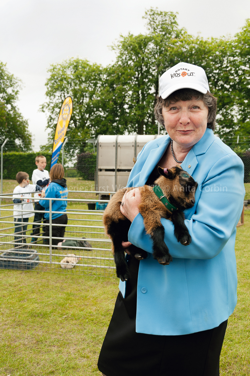 A woman wearing a blue blazer and white cap standing outside holding a baby goat.