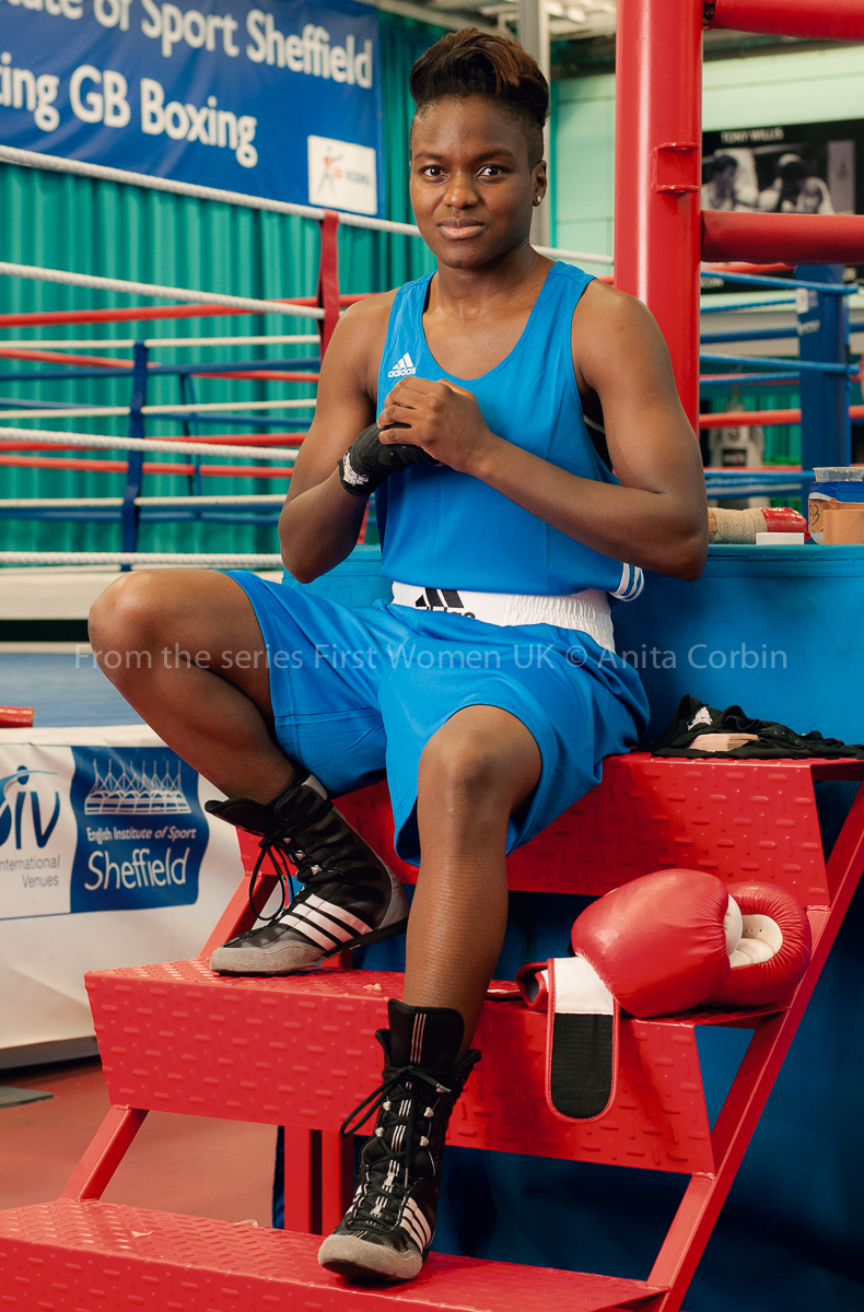 Woman wearing blue wresting gear sitting on red steps leading to a boxing ring.