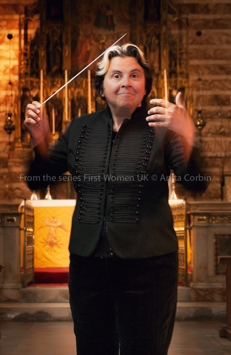 A woman conducting, dressed in black.