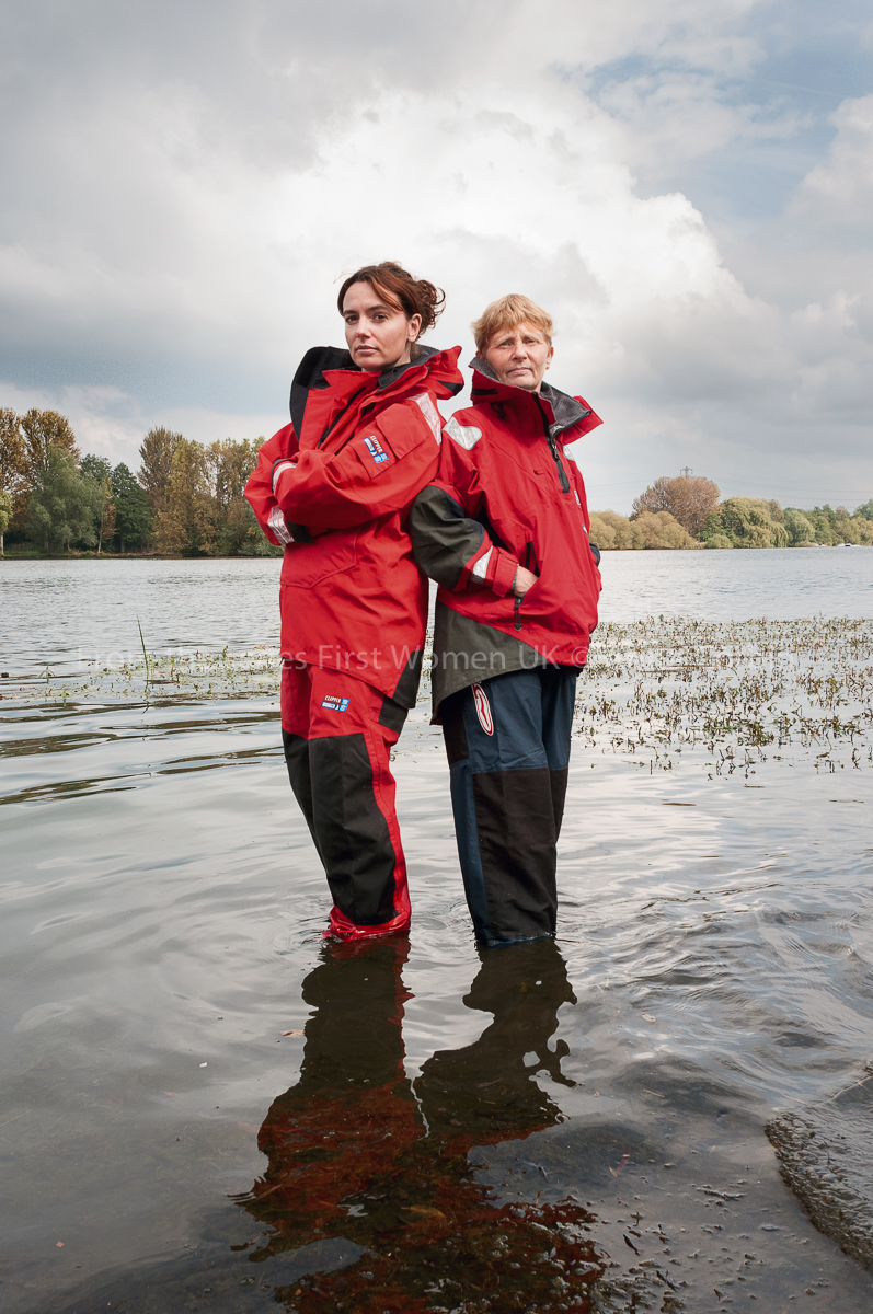 Two Women in red waterproof coats standing back-to-back in a flooded area.