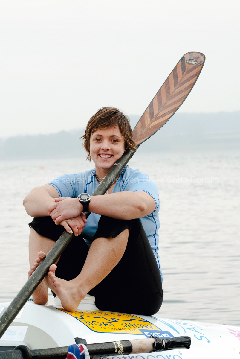 A woman in a light blue top sitting on a rowing boat with an oar over her left shoulder.