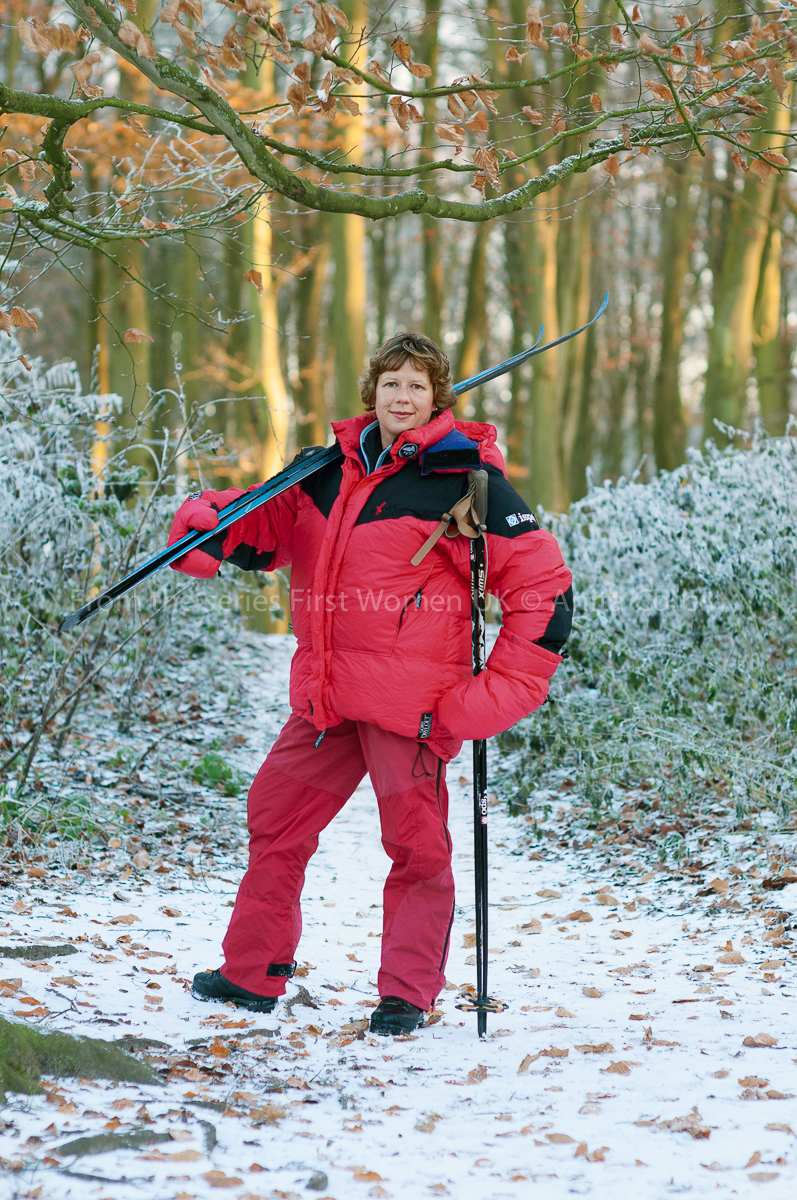 Woman wearing a large red winter coat and matching trousers with skis over her right shoulder. A light dusting of snow on the ground and bushes in the background..