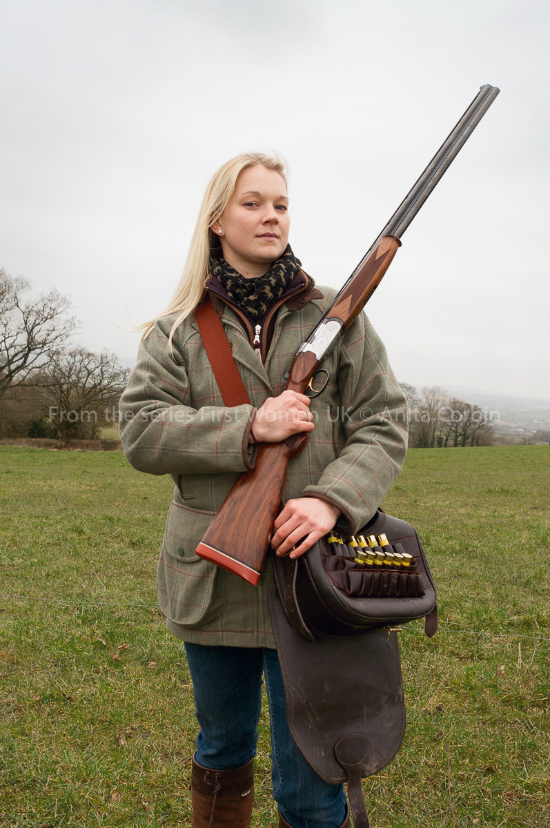 A woman in a field holding a rifle over her shoulder.