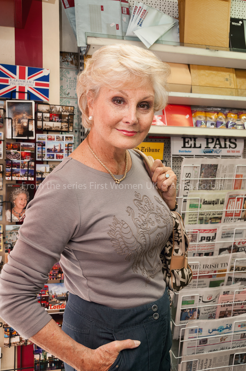 A woman wearing a grey top standing in a newsagents in front of a stand of postcards and newspapers.