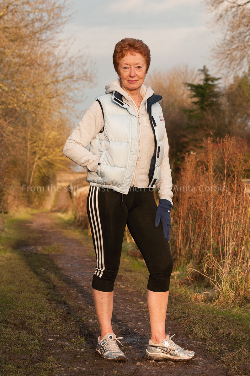 A woman standing in an outdoor footpath wearing activewear.