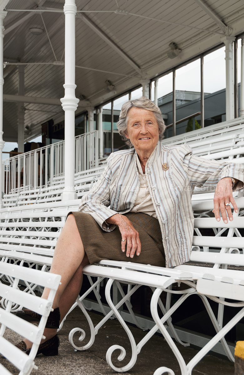 Woman sitting on a white bench in a row of bleachers. She is wearing a brown skirt and a white and grey striped blazer.