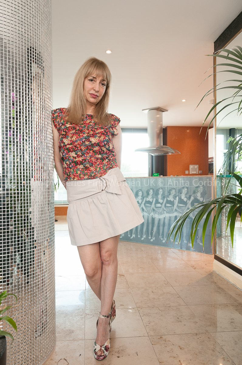 Woman wearing a multicoloured top and white skirt leaning against a curved silver wall.