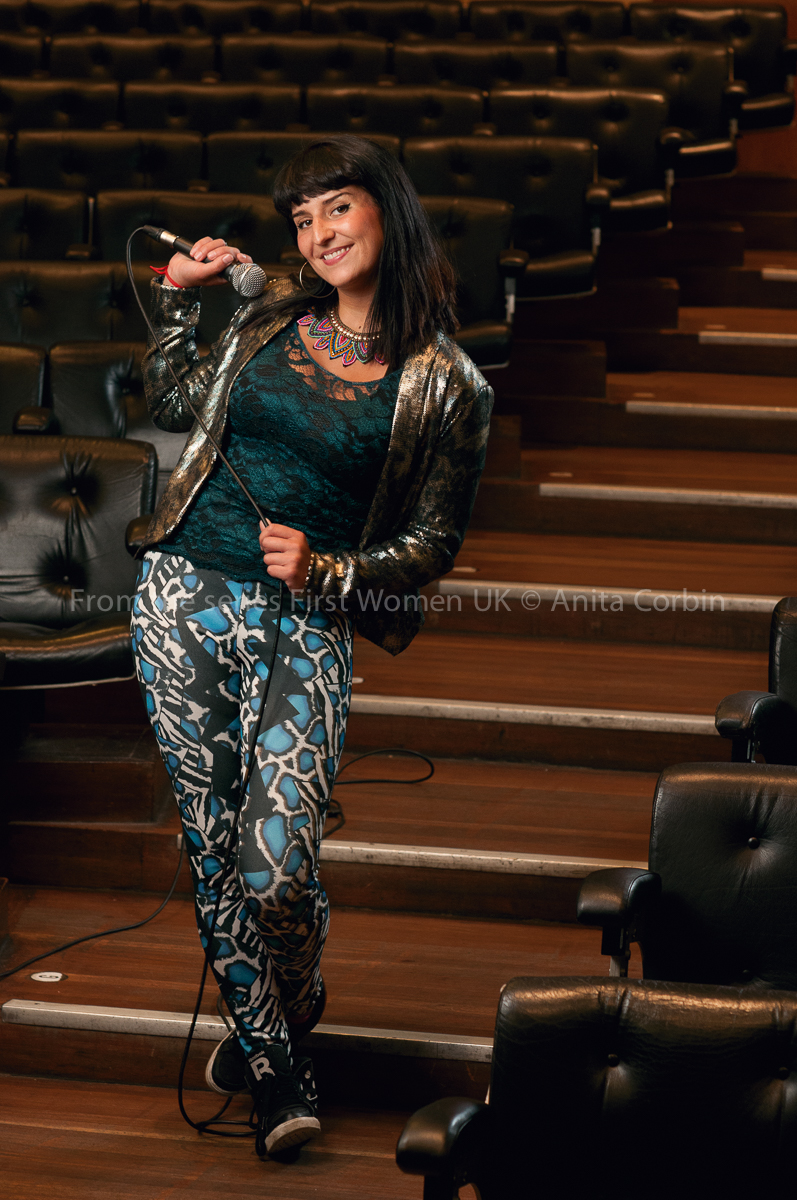 A woman wearing blue leopard print trousers and a green and black top with a bronze jacket standing on the steps of an auditorium holding a microphone.