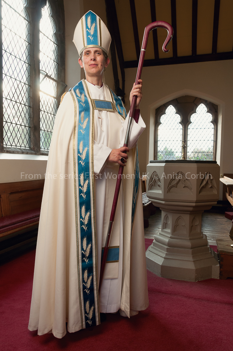 A woman wearing a white and blue bishop's uniform standing in a church in front of the altar.
