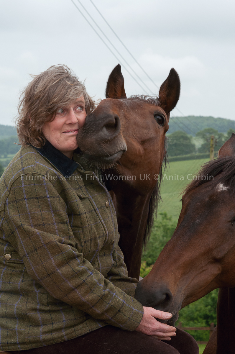 A woman sitting outdoors with two horses. One has its face in her hand and the other's face is touching hers.