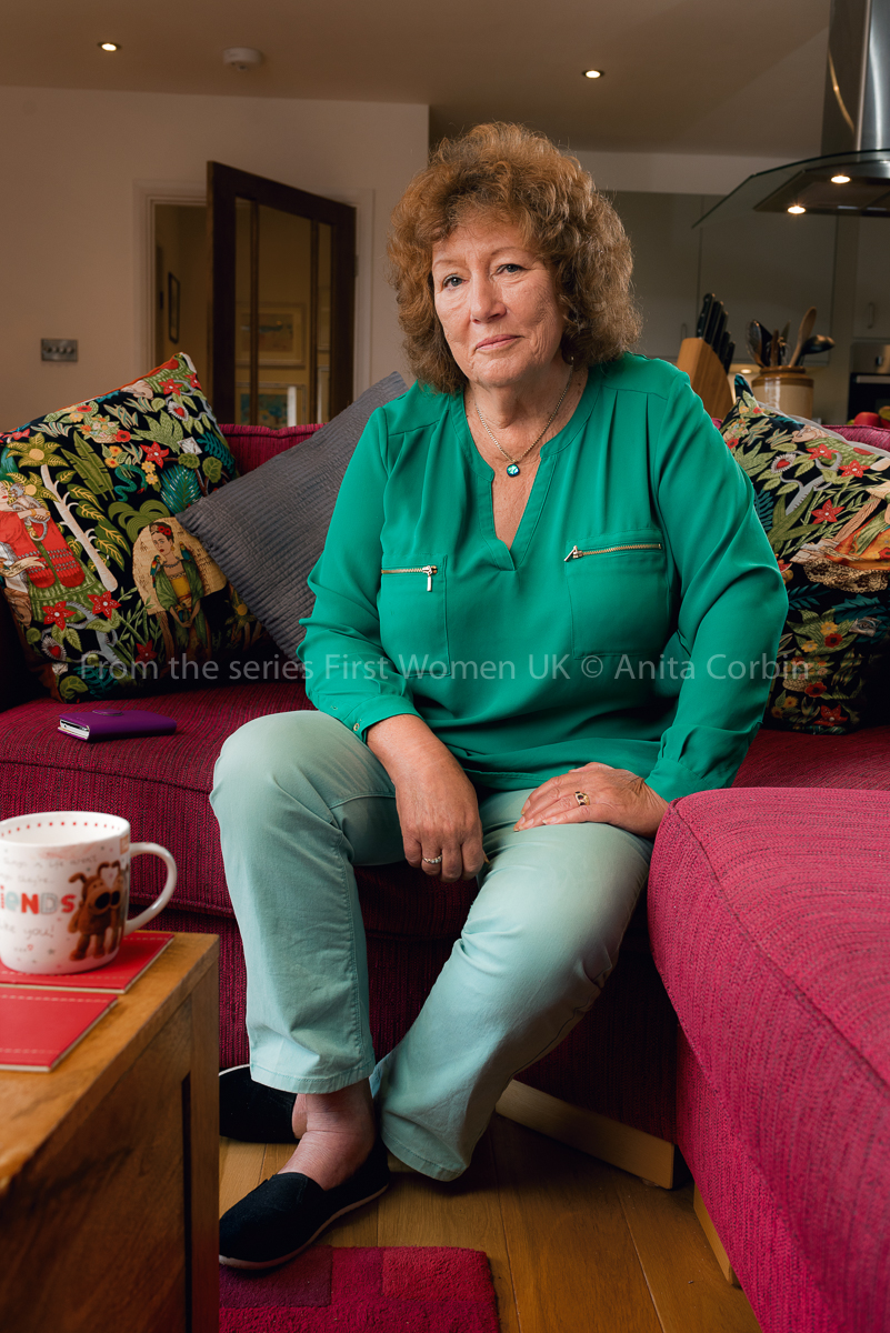 A woman wearing a bright green shirt sitting on a pink sofa.