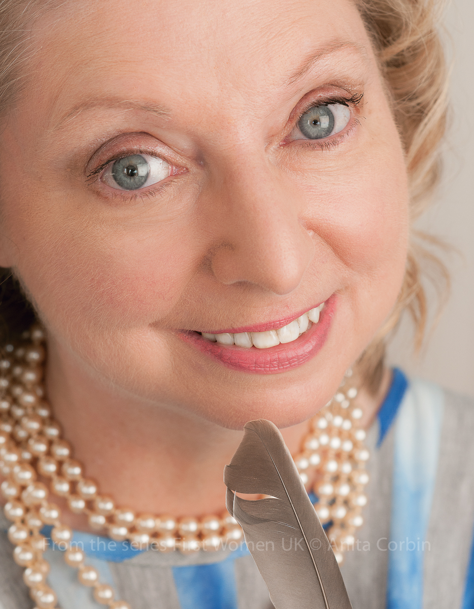A close up of a woman's face. She has blue eyes and is wearing a pearl necklace.