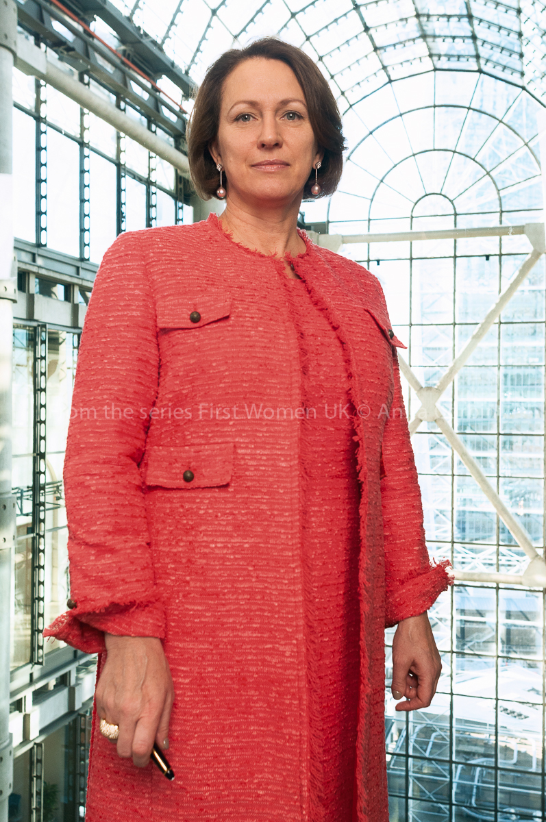 A woman wearing a red dress and matching jacket standing in a large glass building with a pen in her right hand.