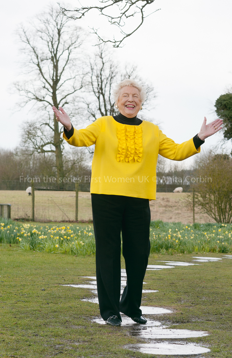A woman wearing a bright yellow jumper and black trousers standing with her arms open outside.