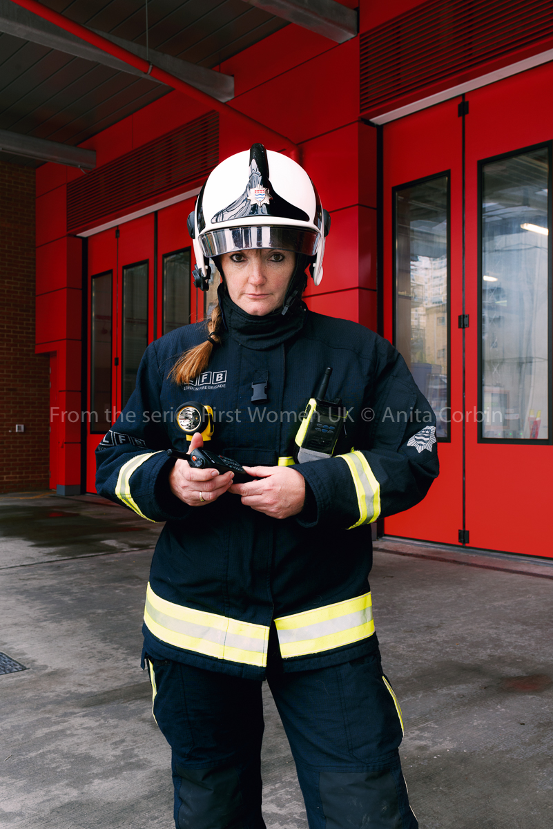 A woman wearing firefighter uniform standing in front of a fire station.