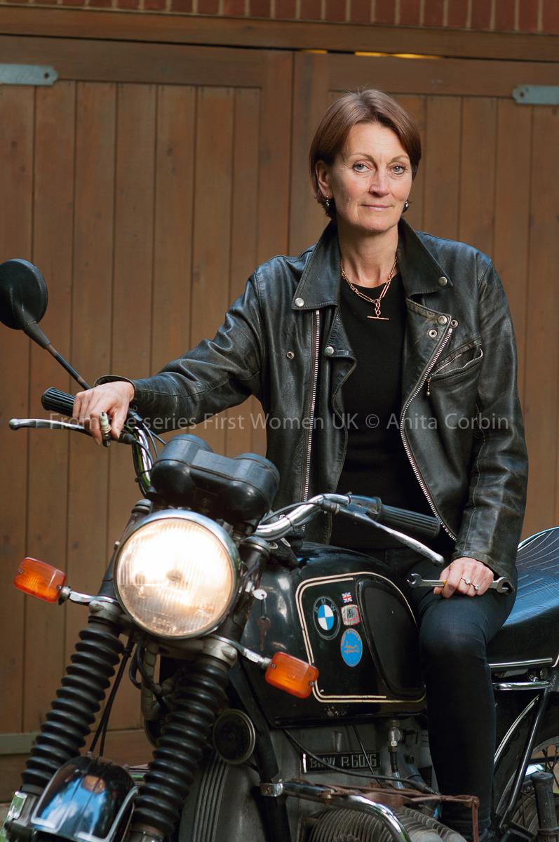 A woman wearing a black leather jacket sitting on a motorbike.