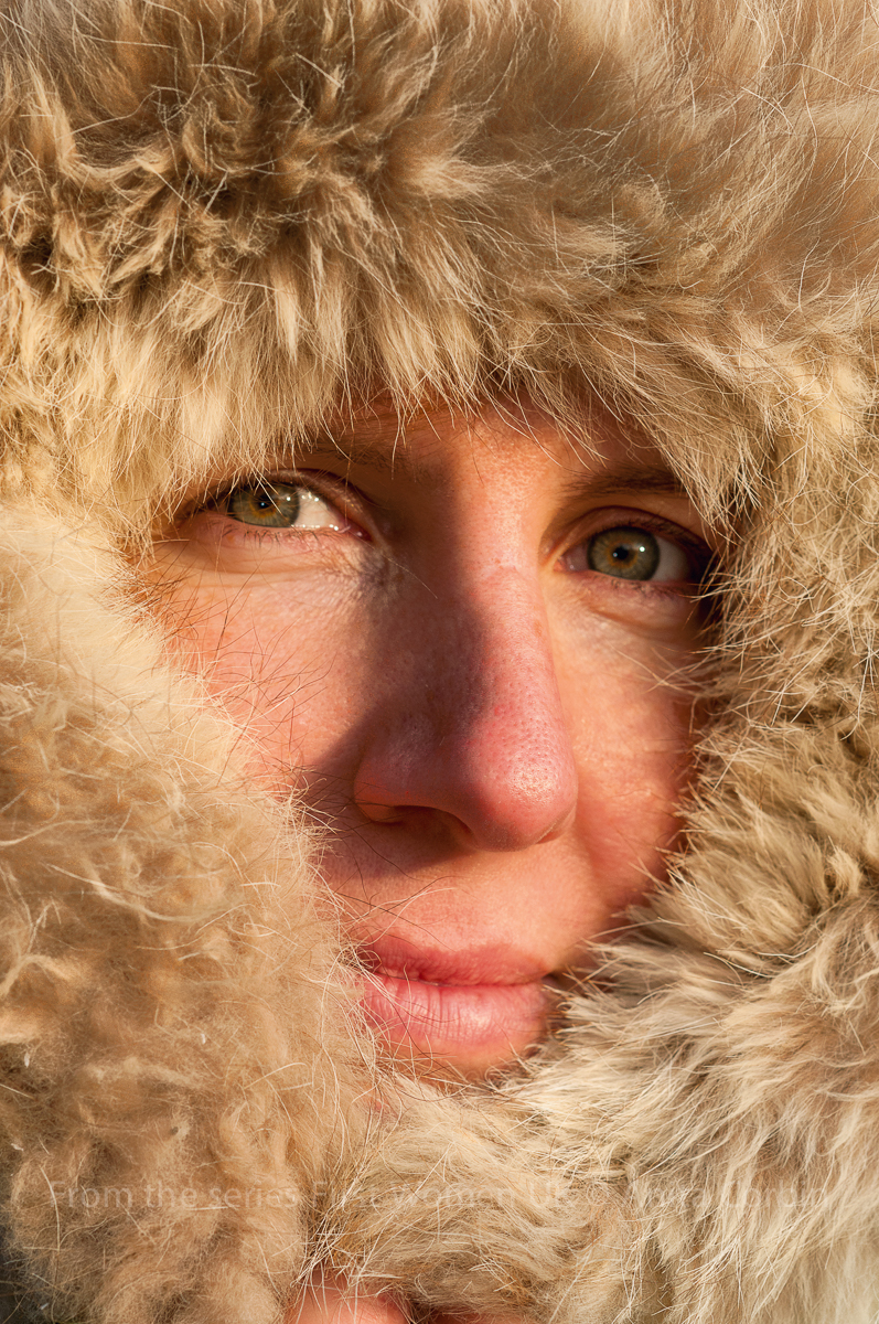 A close up of a woman's face with a fur hood covering all of her face apart from her eyes, nose and mouth.