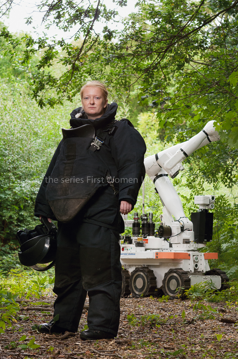 Woman wearing bomb disposal uniform standing outside with a large white machine in the background.