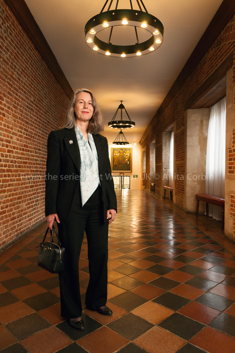 A woman wearing a suit standing in a brick hallway with brown tiles. She is holding a small black bag in her right hand.