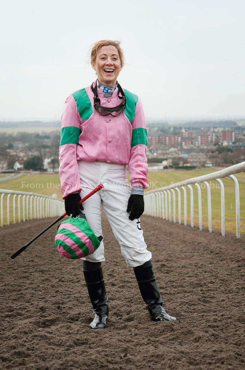A woman standing in the middle of a horse racing track wearing a pink and green jockey outfit.