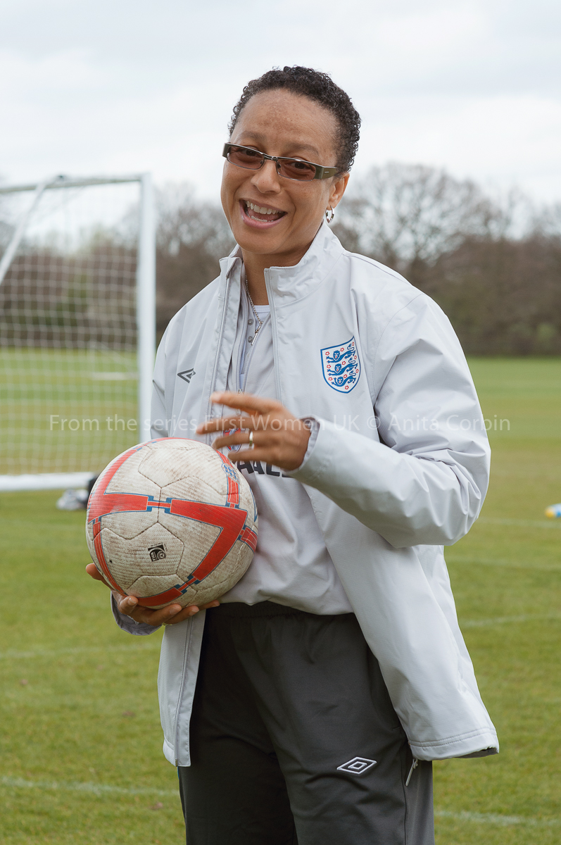 A woman holding a football and wearing an England football team jacket. She is standing on a football pitch with a goal behind her.