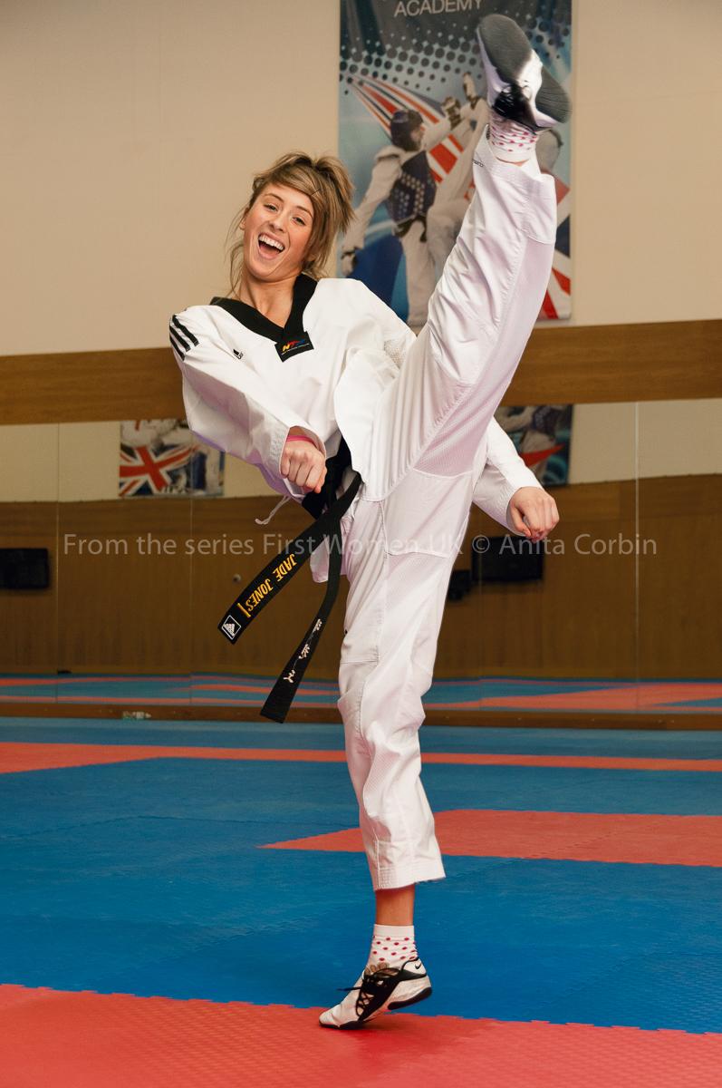 A woman in karate uniform kicking her leg in the air.